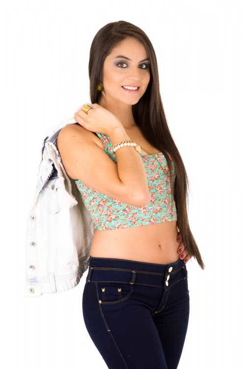 Woman wearing a crop top holding a shopping. bag.