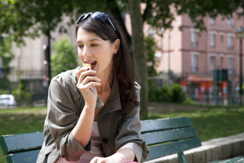Woman having a snack in a park.