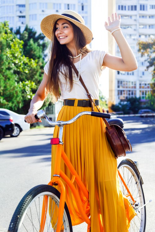 Woman wearing a maxi skirt riding a bike.