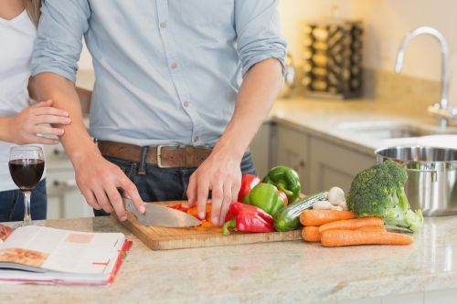 Man chopping vegetables in the kitchen.
