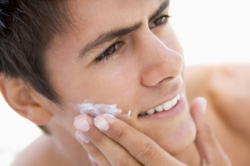 Guy moisturizing his face.