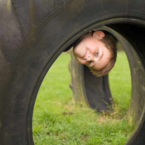 Child looking through a tyre in an obstacle course.