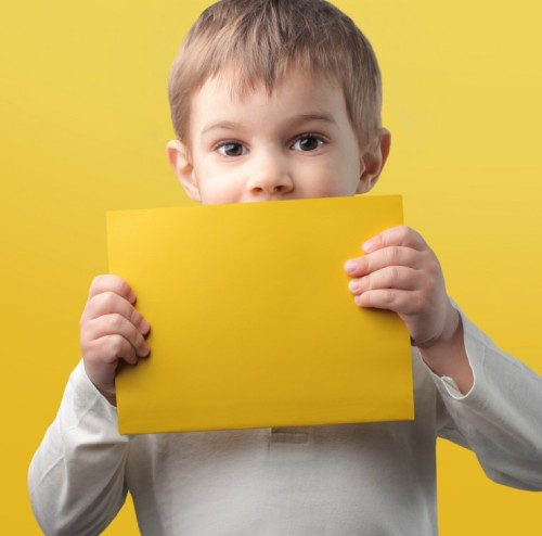 Child holding a yellow sheet of paper.