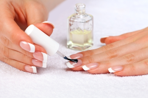 Woman applying a base coat on her nails.