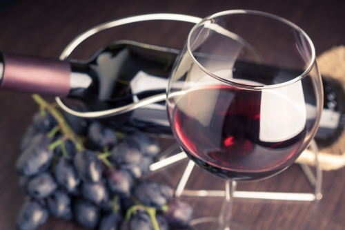 Red wine and red grapes on a wooden table.