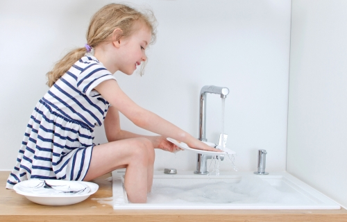 Young girl washing the dishes.
