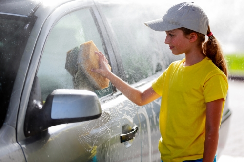 Young girl washing a car.