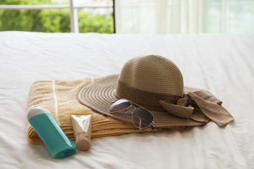 Sunscreen, sunglasses and hat on a bed. Packing for the beach.