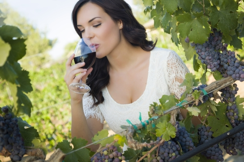 Woman sipping on wine in a vineyard.