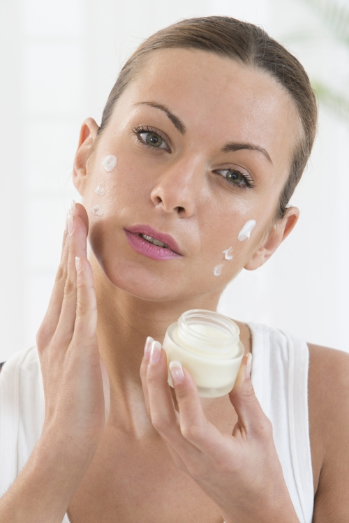 Woman moisturizing face.