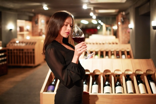 Woman tasting red wine