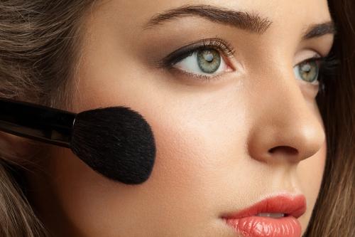 Woman applying makeup.