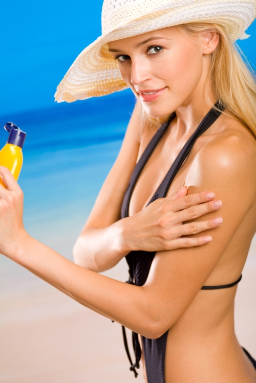 Woman applying sunscreen.