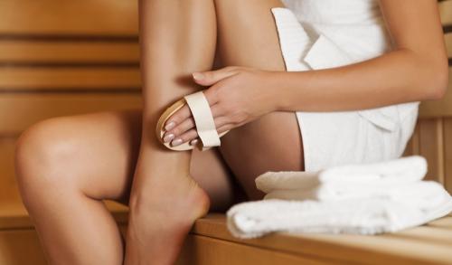 Woman brushing her legs.