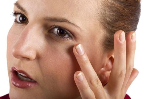 Woman applying concealer.
