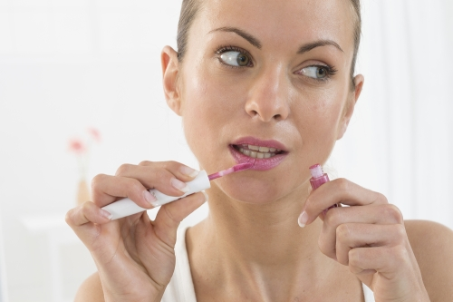 Woman applying pink lipstick.