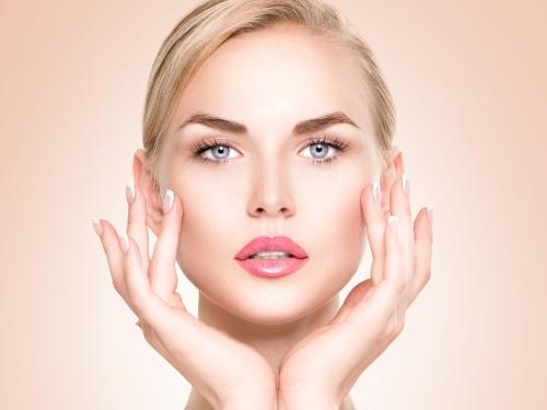 Woman applying serum around her eyes