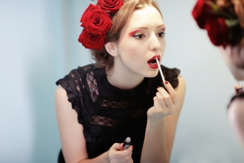 Woman applying lipstick.