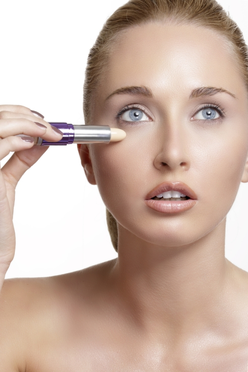 Woman applying concealer.