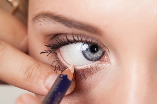 Woman applying white eyeliner