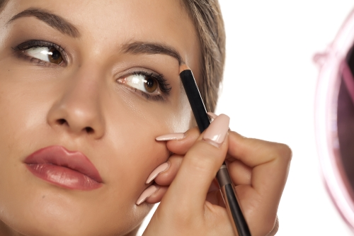 Woman using brow pencil