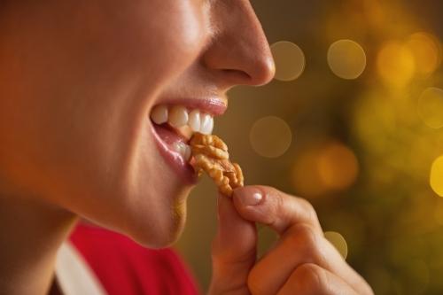 Woman eating walnut.