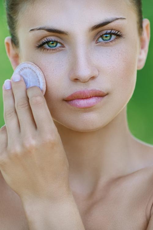 Woman moisturizing skin