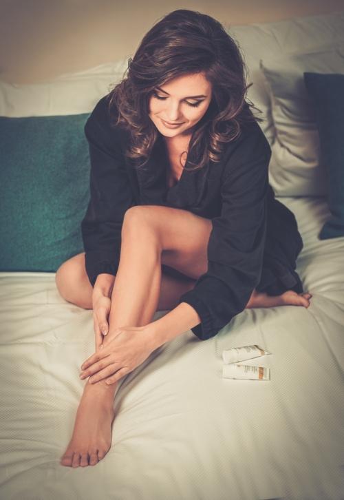 Woman moisturizing legs