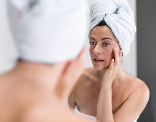 middle aged women examining her wrinkles in mirror.