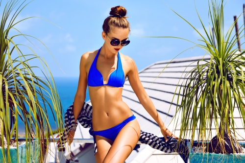 Woman in a bikini with a topknot hairstyle