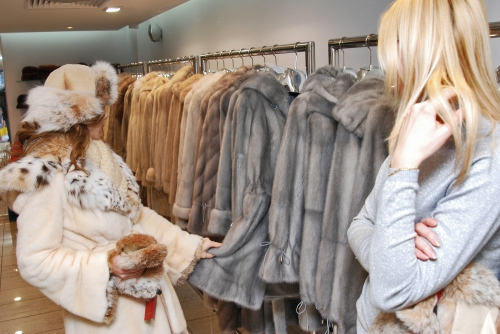 woman viewing a selection of fur coats