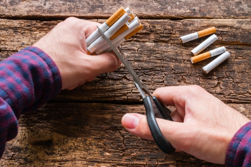 Man cutting cigarettes in half