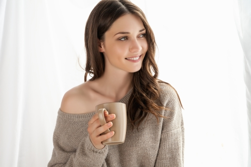 Woman drinking coffee indoors
