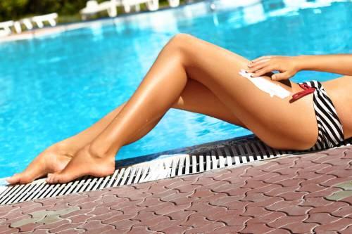 woman applying sunscreen on legs