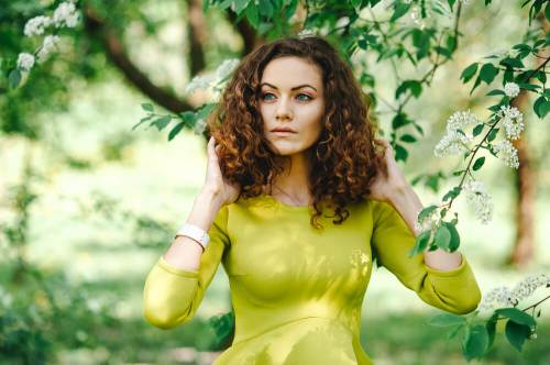 woman in green with curly hair